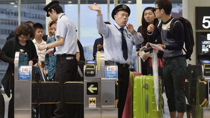 Travelers ask station staff for the alternative transportation after the train service all around the Osaka metropolitan area is suspended because of approaching Typhoon Vongfong in Osaka, western Japan, Monday, Oct. 13, 2014. The typhoon was downgraded to a tropical storm as it hit the Japanese island of Kyushu after battering the southern island of Okinawa. Train service and flights were disrupted in southwestern Japan. (AP Photo/Kyodo News) JAPAN OUT, CREDIT MANDATORY