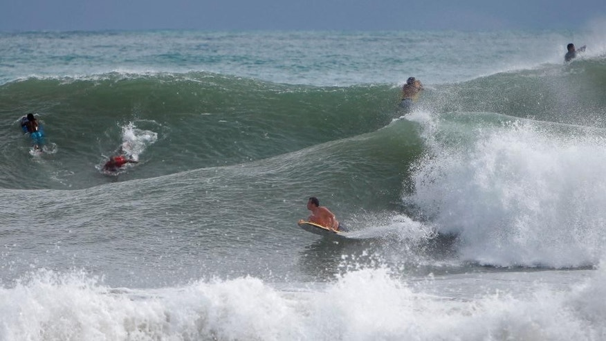 Surfers ride the waves in the waters at La Pared Beach in Luquillo, Puerto Rico, Tuesday, Oct. 14, 2014. Hurricane Gonzalo moved away from the area, but churned up heavy surf across much of the Caribbean, Tuesday. Forecasters said it could pick up strength and become a major storm as it approaches Bermuda. (AP Photo/Ricardo Arduengo)