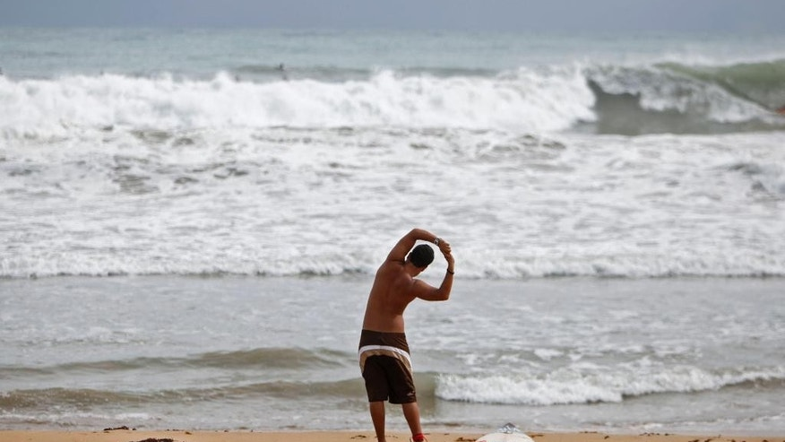 A surfer stretches on the shore of La Pared Beach in Luquillo, Puerto Rico, Tuesday, Oct. 14, 2014. Hurricane Gonzalo moved away from the area, but churned up heavy surf across much of the Caribbean, Tuesday. Forecasters said it could pick up strength and become a major storm as it approaches Bermuda. (AP Photo/Ricardo Arduengo)