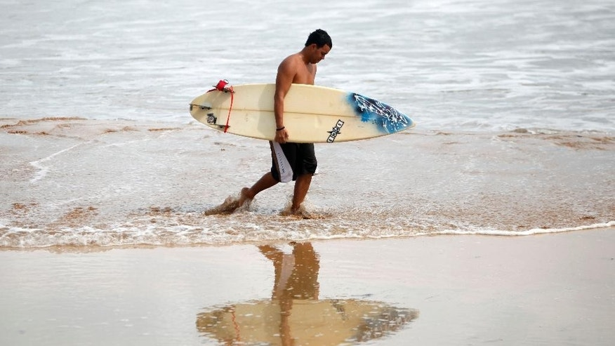 A surfer carries his surfboard as he walks along La Pared Beach in Luquillo, Puerto Rico, Tuesday, Oct. 14, 2014. Hurricane Gonzalo moved away from the area, but churned up heavy surf across much of the Caribbean, Tuesday. Forecasters said it could pick up strength and become a major storm as it approaches Bermuda. (AP Photo/Ricardo Arduengo)