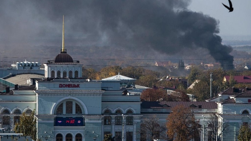 Smoke rises behind Donetsk train station, not far from the Donetsk Sergey Prokofiev International Airport, during an artillery battle between pro-Russian rebels and Ukrainian government forces in the town of Donetsk, eastern Ukraine, Sunday, Oct. 12, 2014. Donetsk airport is the focus of much of the fighting but has no immediate tactical significance for separatist forces who are devoid of any air power. (AP Photo/Dmitry Lovetsky)