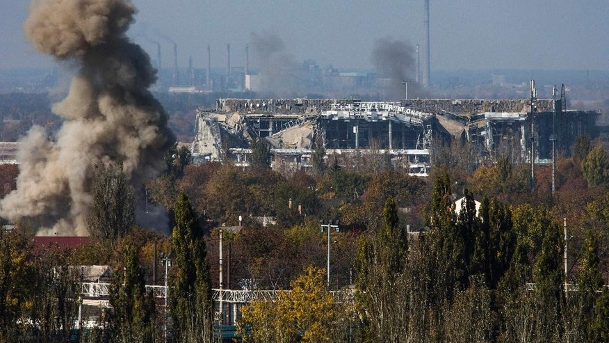 Smoke rises near the main terminal of Donetsk Sergey Prokofiev International Airport during an artillery battle between pro-Russian rebels and Ukrainian government forces in the town of Donetsk, eastern Ukraine, Sunday, Oct. 12, 2014. Donetsk airport is the focus of much of the fighting but has no immediate tactical significance for separatist forces who are devoid of any air power. (AP Photo/Dmitry Lovetsky)