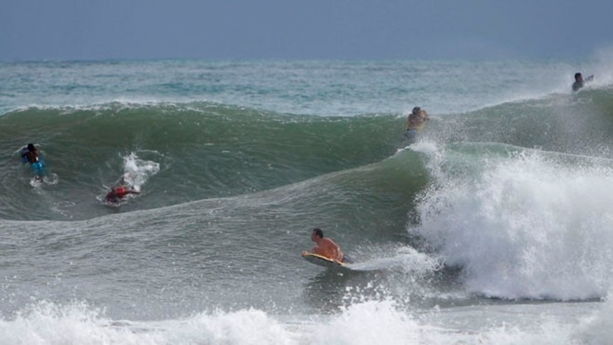 Oct. 14, 2014: Surfers ride the waves in the waters at La Pared Beach in Luquillo, Puerto Rico. (AP)
