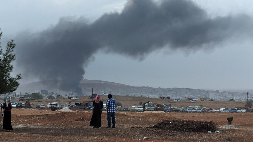 Residents of Mursitpinar on the outskirts of Suruc, at the Turkey-Syria border, watch as thick smoke rises following an airstrike by the US-led coalition in Kobani, Syria while fighting continued between Syrian Kurds and the militants of Islamic State group, Tuesday, Oct. 14, 2014. Kobani, also known as Ayn Arab, and its surrounding areas, has been under assault by extremists of the Islamic State group since mid-September and is being defended by Kurdish fighters. (AP Photo/Lefteris Pitarakis)