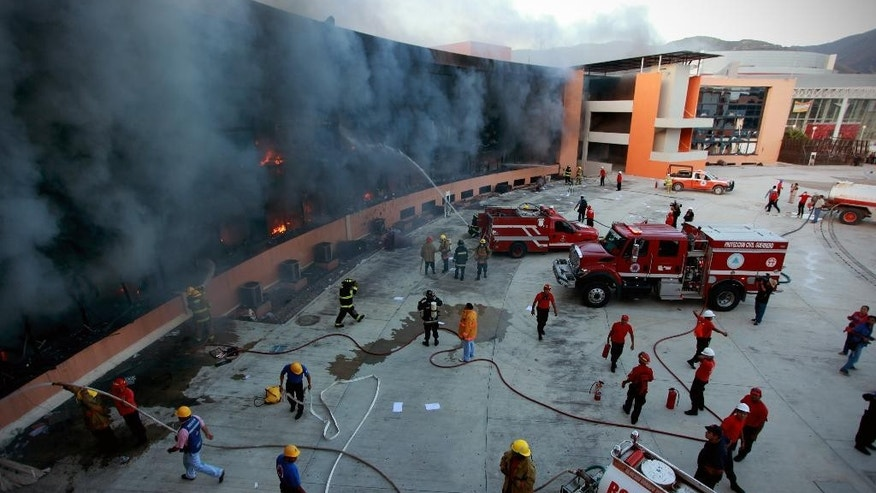 Firefighters try to extinguish the flames after the state capital building was set on fire by protesting college students in Chilpancingo, Mexico, Monday Oct. 13, 2014. Hundreds of protesting teachers and students demanding answers about the 43 students who went missing on Sept. 26 during a confrontation with police, clashed with police at the local congress and outside the state government palace Monday. Officials are attempting to determine if any of the missing students are in newly discovered mass graves. (AP Photo/Felix Marquez)