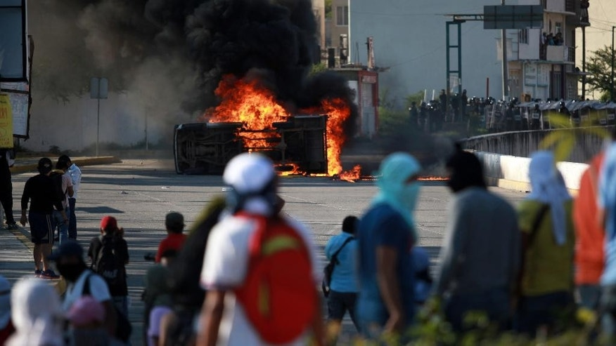 A burning overturned car stands between protesting students and riot police after it was set on fire by protesting college students outside of the Guerrero state capital building in Chilpancingo, Mexico, Monday Oct. 13, 2014. Hundreds of protesting teachers and students demanding answers about the 43 students who went missing on Sept. 26 during a confrontation with police, clashed with police at the local congress and outside the state government palace Monday. Officials are attempting to determine if any of the missing students are in newly discovered mass graves. (AP Photo/Felix Marquez)