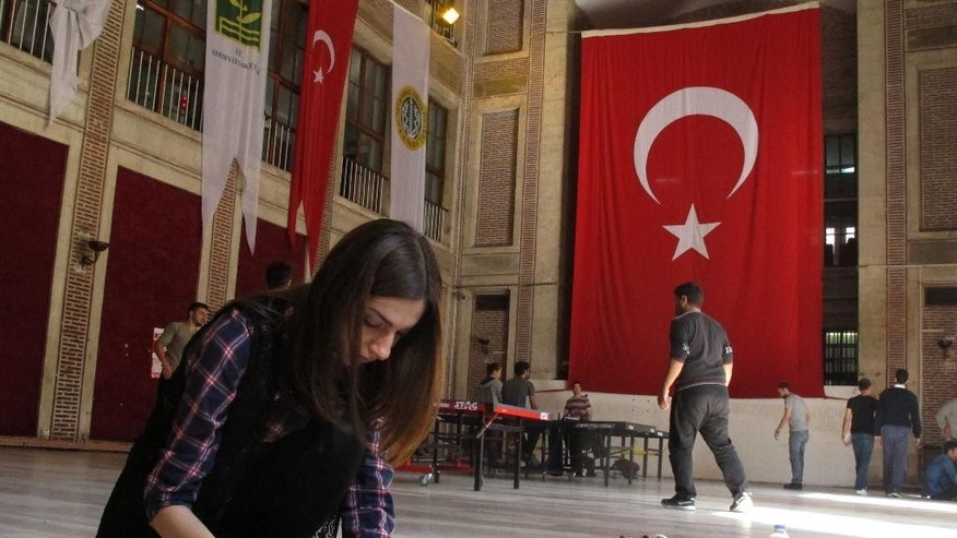 In this photo taken Tuesday, Sept. 30, 2014, a student puts the finishing touches on an anti-Islamic State poster at Istanbul University's Department of Literature, Istanbul, Turkey. The student was one of several critical of the militant group, whose supporters clashed with left-wing students on Friday, Sept. 26, 2014. The violence was one of the clearest signs that the radical Islamic State group has found sympathizers in Istanbul. (AP Photo/Raphael Satter)