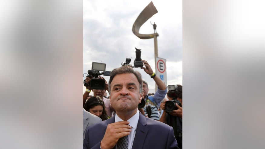 In this Oct. 8, 2014 photo, Aecio Neves, Brazilian Social Democracy Party presidential candidate, straightens his tie as he arrives to a campaign rally at the Memorial JK that honors former Brazilian President Juscelino Kubitschek, in Brasilia, Brazil. Neves turned Brazil's politics on its head with his surprise showing in the first round of presidential voting but his toughest task lies ahead - defeating incumbent Dilma Rousseff and her juggernaut Workers' Party which has governed for 12 years. (AP Photo/Eraldo Peres)