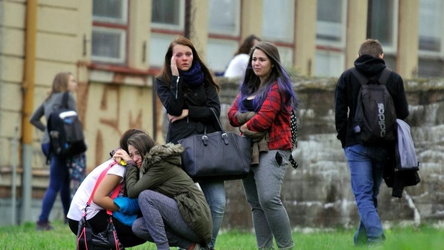 Girls comfort each others near a high school where a woman stabbed and killed a student and injured two other others in Zdar nad Sazavou, 120 kilometers (75 miles) southeast of Prague, on Tuesday, Oct. 14, 2014. Police spokeswoman Jana Kroutilova says the victim was a 16-year old boy. She says the 26-year-old female suspect also injured two teenage girls and a police officer before she was arrested. Police say the suspect was from a different Czech region and it was not immediately clear why she attacked the students. (AP Photo/CTK, Lubos Pavlicek) SLOVAKIA OUT