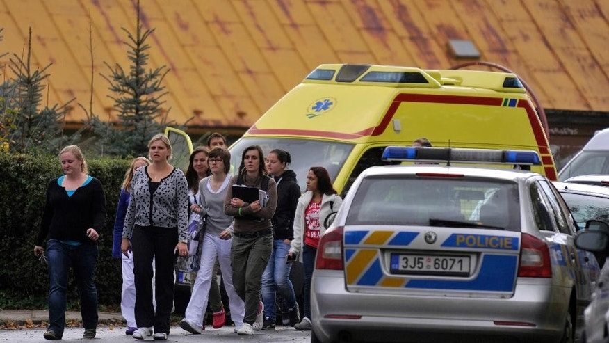 Students pass police cars and an ambulace near their high school where a woman stabbed and killed a teenager and injured two other students in Zdar nad Sazavou, 120 kilometers (75 miles) southeast of Prague, Tuesday, Oct. 14, 2014. Police spokeswoman Jana Kroutilova says the victim was a 16-year old boy. She says the 26-year-old female suspect also injured two teenage girls and a police officer before she was arrested. Police say the suspect was from a different Czech region and it was not immediately clear why she attacked the students. (AP Photo/CTK, Lubos Pavlicek) SLOVAKIA OUT