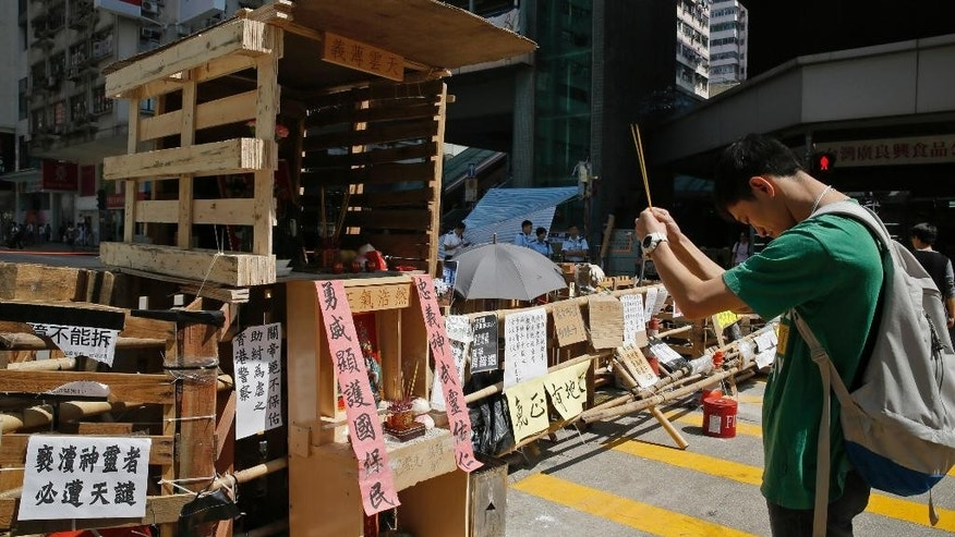 "In this Saturday, Oct. 11, 2014 photo, a man pays respect to a mini shrine set up on the spot for the Chinese folk hero and deity Guan Yu at barricades that protesters have set up to block off main roads in Mong Kok district in Hong Kong. The shrine is a clever response after several nights of brawling and violent clashes between protesters, police and angry mobs. Mong Kok is a haven for Hong Kong's triads, or organized crime gangs, but neither mobsters nor police would want to offend Guan Yu, a figure adopted by both sides as their guardian deity. The Chinese words read: ""The power of loyalty and justice protect us,"" left, and ""Righteousness abounds."" (AP Photo/Vincent Yu)"