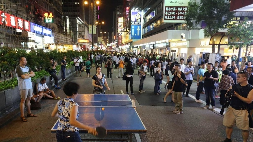 "In this Thursday, Oct. 9, 2014 photo, people play ping-pong at a blocked off main roads in Mong Kok district in Hong Kong. Police were quick to seize on the episode to condemn the protesters, and a pro-Beijing newspaper put the photos on its front page. ""Illegal occupiers are occupying the roads as their living space and playground,"" said a police spokesman. (AP Photo/Apple Daily) HONG KONG OUT, TAIWAN OUT"