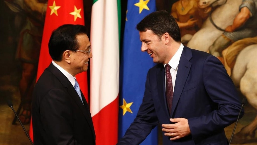 Chinese Prime Minister Li Keqiang, left, and Italian Premier Matteo Renzi shake hands after giving a joint a press conference at the end of their meeting at Chigi Palace government office in Rome, Tuesday, Oct. 14, 2014. (AP Photo/Riccardo De Luca)