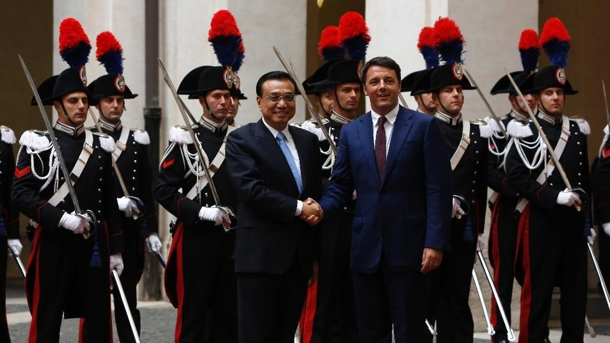 Italian Premier Matteo Renzi and Chinese Prime Minister Li Keqiang, left, shake hands for photographers in the courtyard of Chigi Palace government office in Rome, Tuesday, Oct. 14, 2014. (AP Photo/Riccardo De Luca)
