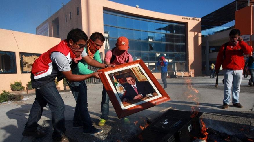 College Students burn a portrait of Guerrero state governor Angel Aguirre as they trash and later set on fire the state capital building  in Chilpancingo, Mexico, Monday Oct. 13, 2014. Hundreds of protesting teachers and students demanding answers about the 43 students who went missing on Sept. 26 during a confrontation with police, clashed with police at the local congress and outside the state government palace Monday. Officials are attempting to determine if any of the missing students are in newly discovered mass graves. (AP Photo/Felix Marquez)