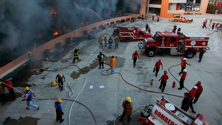 Oct. 13, 2014: Firefighters try to extinguish the flames after the state capital building was set on fire by protesting college students in Chilpancingo, Mexico