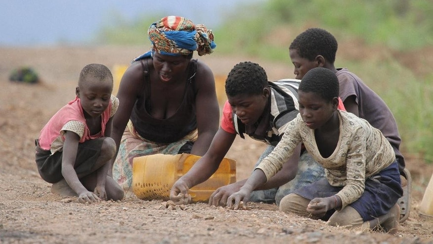 File: In this file photo taken Saturday, Nov. 2, 2013, a woman and children colect stones from roadside sand to sell as building material, in Inchope, northern Mozambique. The country goes to the polls Wednesday, Oct. 15, 2014, with the winners of the election set to control natural resources in the northern part of the country worth billions of dollars.  (AP Photo/Tsvangirayi Mukwazhi, File)