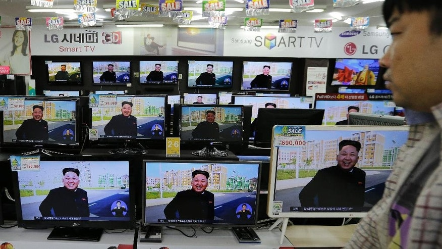 A shopper walks by TV monitors showing a news report about North Korean leader Kim Jong Un, at an electronic shop, South Korea, Tuesday, Oct. 14, 2014. Kim has made his first public appearance in five weeks, state media reported Tuesday, ending an absence that drove a frenzy of global speculation that something was amiss with the country's most powerful person. (AP Photo/Ahn Young-joon)