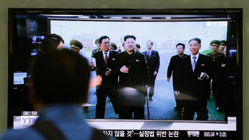 ADDS WHERE KIM APPEARED - A man watches a TV news program at the Seoul Railway Station in Seoul, South Korea, Tuesday, Oct. 14, 2014, showing North Korean leader Kim Jong Un using a cane, reportedly during his first public appearance in five weeks in Pyongyang, North Korea. Kim has made his first public appearance in five weeks, smiling broadly and supporting himself with a cane while touring the newly built Wisong Scientists Residential District and another new institute in Pyongyang, state media reported Tuesday, ending an absence that drove a frenzy of global speculation that something was amiss with the country's most powerful person. (AP Photo/Lee Jin-man)