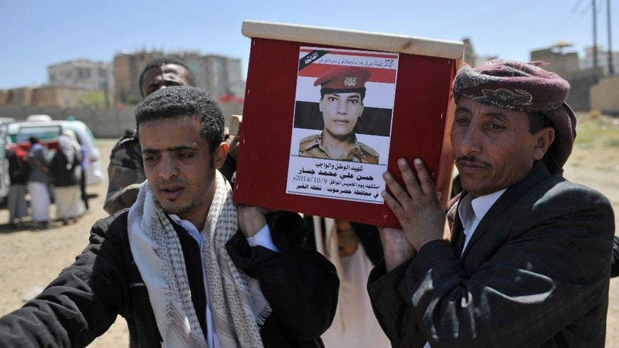 "Yemeni mourners carry the coffin of a soldier who was killed Thursday when a suicide car bomber rammed a security outpost on the outskirts of the port city of Mukalla, during his funeral, in Sanaa, Yemen, Monday, Oct. 13, 2014. Two suicide bombers struck in Yemen on Thursday — one targeting a gathering of Shiite rebels in Sanaa, the country's capital and the other hitting a military outpost in Mukalla in the south — in attacks that killed nearly 70 people, officials said. Arabic writing on coffin reads in part, ""Martyr of country and duty, Hassen Ali Mohammed Jassar, killed on Thursday, Oct. 9, 2014, in Hadramout province."" (AP Photo/Hani Mohammed)"