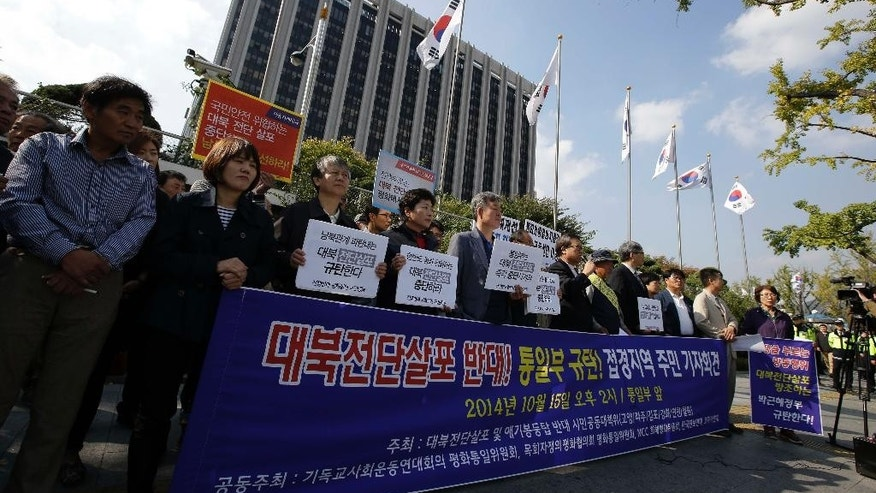 "South Korean civic group members and residents in a border area, hold banners demanding protesters to stop sending balloons with anti-Pyongyang propaganda leaflets to North Korea, in front of the government complex in Seoul, South Korea, Wednesday, Oct. 15, 2014. Military generals from North and South Korea met at a border village Wednesday for talks on how to ease animosities between the rival countries following two shooting incidents last week, South Korean media said. The two Koreas traded gunfire Friday after South Korean activists floated balloons carrying the leaflets across the border. The banner read: ""Opposite, Sending anti-Pyongyang propaganda leaflets, and Denounce, Unification Ministry."" (AP Photo/Lee Jin-man)"