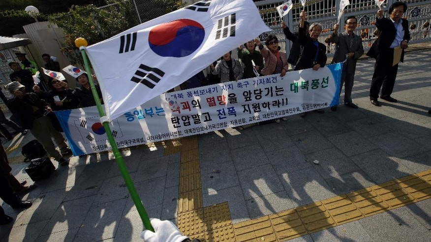 South Korean civic group members wave their national flags as they support sending balloons to North Korea, with anti-Pyongyang propaganda leaflets in front of the government complex in Seoul, South Korea, Wednesday, Oct. 15, 2014. Military generals from North and South Korea met at a border village Wednesday for talks on how to ease animosities between the rival countries following two shooting incidents last week, South Korean media said. The two Koreas traded gunfire Friday after South Korean activists floated balloons carrying the leaflets across the border. (AP Photo/Lee Jin-man)
