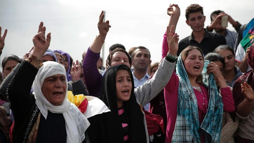 Mourners chant slogans during the funeral of four female Kurdish fighters, killed in the fighting with the militants of the Islamic State group in Kobani, Syria, at a cemetery in Suruc, on the Turkey-Syria border, Tuesday, Oct. 14, 2014. Kobani, also known as Ayn Arab, and its surrounding areas, has been under assault by extremists of the Islamic State group since mid-September and is being defended by Kurdish fighters. (AP Photo/Lefteris Pitarakis)
