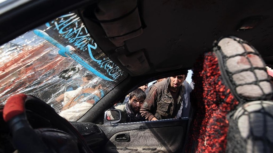 Afghans look inside a civilian vehicle that was damaged in a roadside bombing, in Kabul, Afghanistan, Tuesday, Oct. 14, 2014. The Afghan interior ministry said that several Afghan civilians have been killed and wounded in the bomb blast in the western part of the country's capital. (AP Photo/Massoud Hossaini)