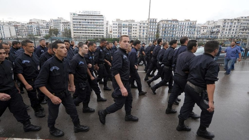 Some 150 members of Algeria's police force stage an unprecedented march through the Algerian capital, Algiers, Tuesday, Oct. 13, 2014, in solidarity with their colleagues in the south. Wearing blue uniforms but without weapons or armor, the riot police marched silently along the highway from their barracks into Algiers, through the rain and to the seat of the government where they were briefly met by the local governor. The police said privately they were marching in solidarity with their embattled colleagues in Ghardaia who face daily attacks as they struggle to keep apart warring Berber and Arab communities. (AP Photo/Sidali Djarboub)