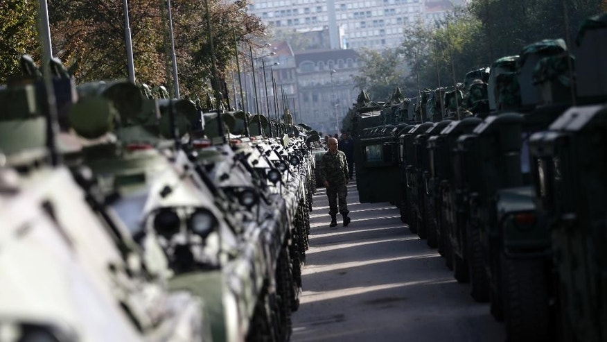 A Serbian army soldier walks alongside armored personal carriers parked in Usce park, two days before an upcoming military parade, in Belgrade, Serbia, Tuesday, Oct. 14, 2014. Serbia is preparing to stage a hero's welcome for Russian President Vladimir Putin with the country's first military parade in 30 years - the red carpet reception considered by some in the West as highly inappropriate for the leader accused of warmongering in Ukraine. (AP Photo/Darko Vojinovic)