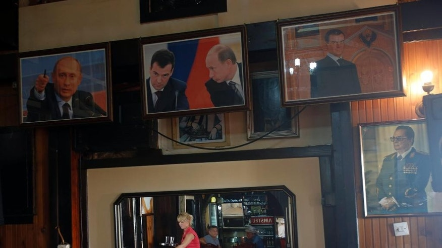 Guests and a waitress are reflected in a mirror at a restaurant decorated with pictures of Russian president Vladimir Putin, left, prime minister Dmitry Medvedev, center, and former Yugoslavian president Josip Broz Tito, lower right, in Belgrade, Serbia, Tuesday, Oct. 14, 2014. Serbia is preparing to stage a hero's welcome for Russian President Vladimir Putin with the country's first military parade in 30 years _ the red carpet reception considered by some in the West as highly inappropriate for the leader accused of warmongering in Ukraine. (AP Photo/Darko Vojinovic)