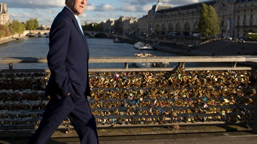 U.S. Secretary of State John Kerry walks across the Seine on the Pont des Arts walking bridge on his way to meet with French Foreign Minister Laurent Fabius at the Quai d'Orsay, the Ministry of Foreign and European Affairs, in Paris, France, Monday Oct. 13, 2014. (AP Photo/Carolyn Kaster, Pool)