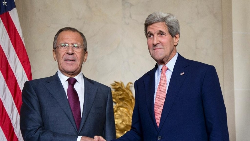 U.S. Secretary of State John Kerry shakes hands with Russian Foreign Minister Sergey Lavrov, left, at the Chief of Mission Residence in Paris, France, Tuesday, Oct. 14, 2014. The top U.S. and Russian diplomats are hoping to find a way to begin reversing a yearlong spike in tensions stemming from Ukraine's revolution and civil war when they meet Tuesday. (AP Photo/Carolyn Kaster, Pool)