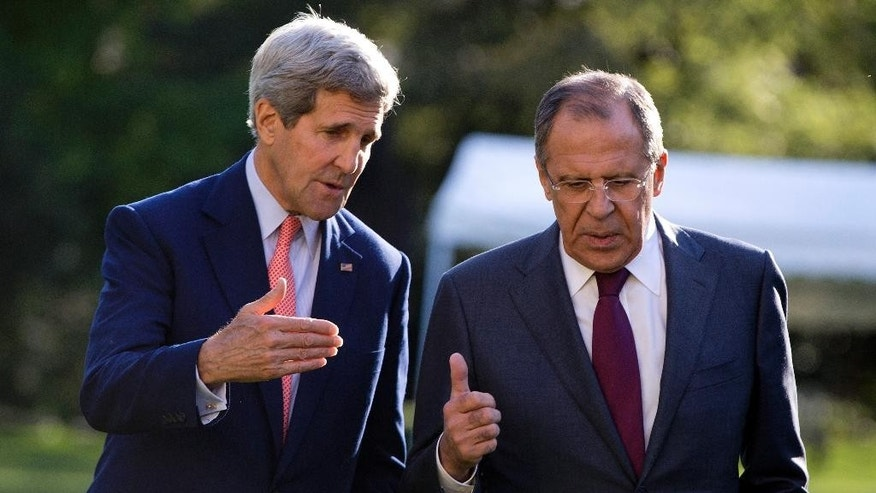 U.S. Secretary of State John Kerry, left, and Russian Foreign Minister Sergey Lavrov talk as they walk together on the grounds of the Chief of Mission Residence in Paris, France, Tuesday, Oct. 14, 2014. The top U.S. and Russian diplomats are hoping to find a way to begin reversing a yearlong spike in tensions stemming from Ukraine's revolution and civil war. (AP Photo/Carolyn Kaster, Pool)