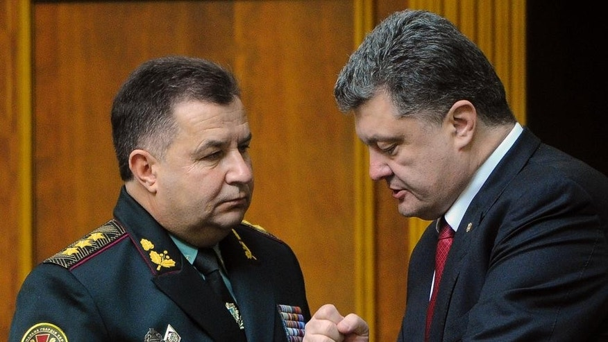 Ukraine's President Petro Poroshenko, right, speaks with new defense minister Stepan Poltorak in parliament in Kiev, Ukraine, Tuesday, Oct. 14, 2014. Ukraine's parliament has approved a new defense minister as the country remains bogged down in daily clashes with pro-Russian separatist forces in its industrial eastern regions. (AP Photo/Andrew Kravchenko, Pool)