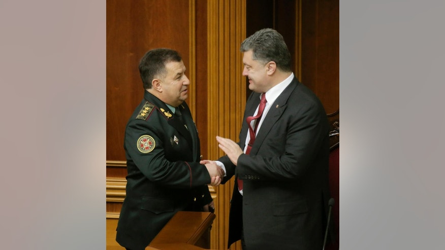 Ukraine's President Petro Poroshenko, right, speaks with new defense minister Stepan Poltorak in parliament in Kiev, Ukraine Tuesday, Oct. 14, 2014. Ukraine's parliament has approved a new defense minister as the country remains bogged down in daily clashes with pro-Russian separatist forces in its industrial eastern regions. (AP Photo/Andrew Kravchenko, Pool)