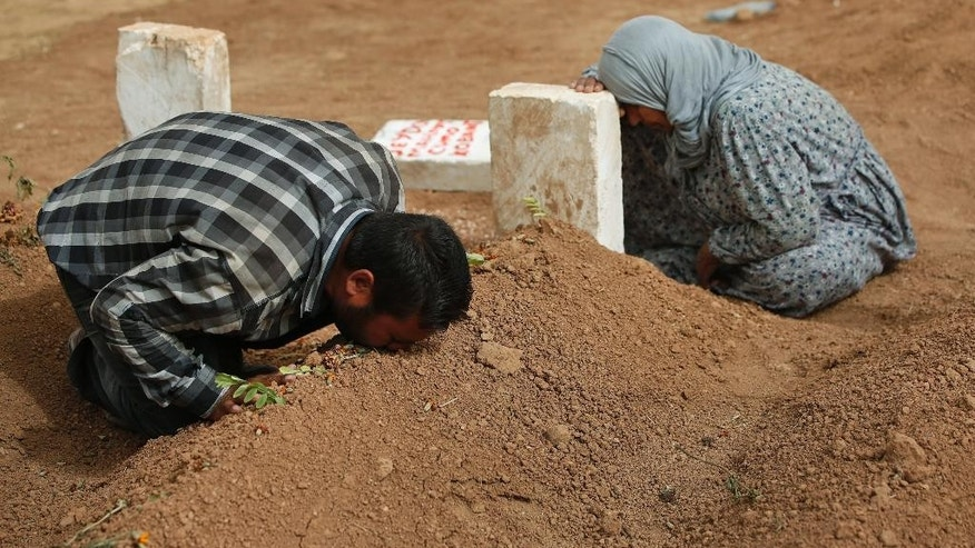 FILE - In this  Saturday, Oct. 11, 2014 file photo, Kurdish Rabia Ali, right, accompanied by her son Ali Mehmud, mourn at the grave of her son Seydo Mehmud 'Curo' , a Kurdish fighter, who was killed in the fighting with the militants of the Islamic State group in Kobani, Syria, and was buried at a cemetery in Suruc, Turkey. No one contests that the U.S.-led coalition has conducted more than 40 airstrikes against the militants besieging Kobani, nor that Turkey has granted refuge to more than 200,000 people who have flooded across the border to escape the offensive. But Kurds say that both countries - and the international community in general - should be doing more to help save Kobani from the fanatical militants who have massacred and beheaded their enemies across Syria and Iraq. (AP Photo/Lefteris Pitarakis, File)