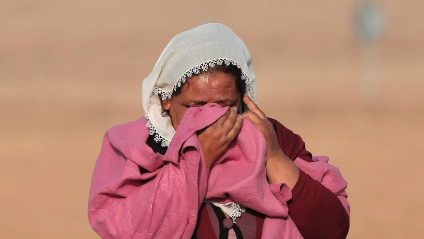 FILE - In this Monday, Oct. 13, 2014 file photo, Syrian Kurd Kiymet Ergun, 56, weeps standing in Mursitpinar, on the outskirts of Suruc, Turkey. No one contests that the U.S.-led coalition has conducted more than 40 airstrikes against the militants besieging Kobani, nor that Turkey has granted refuge to more than 200,000 people who have flooded across the border to escape the offensive. But Kurds say that both countries - and the international community in general - should be doing more to help save Kobani from the fanatical militants who have massacred and beheaded their enemies across Syria and Iraq.(AP Photo/Lefteris Pitarakis)