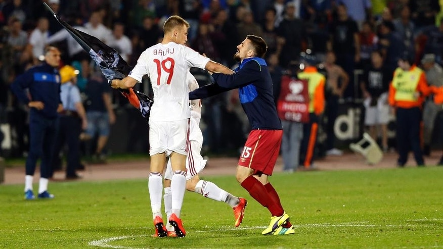 Albania's Bekim Balaj, left, and Serbia's Nenad Tomovic, fight over a flag banner that was suspended by a drone during the Euro 2016 Group I qualifying match between Serbia and Albania at the Partizan stadium in Belgrade, Serbia, Tuesday, Oct. 14, 2014. The 2016 European Championship qualifier between Serbia and Albania was abandoned on Tuesday after skirmishes broke out on the pitch involving players and fans over an Albanian flag that was flown above the stadium by a drone. (AP Photo/Marko Drobnjakovic)