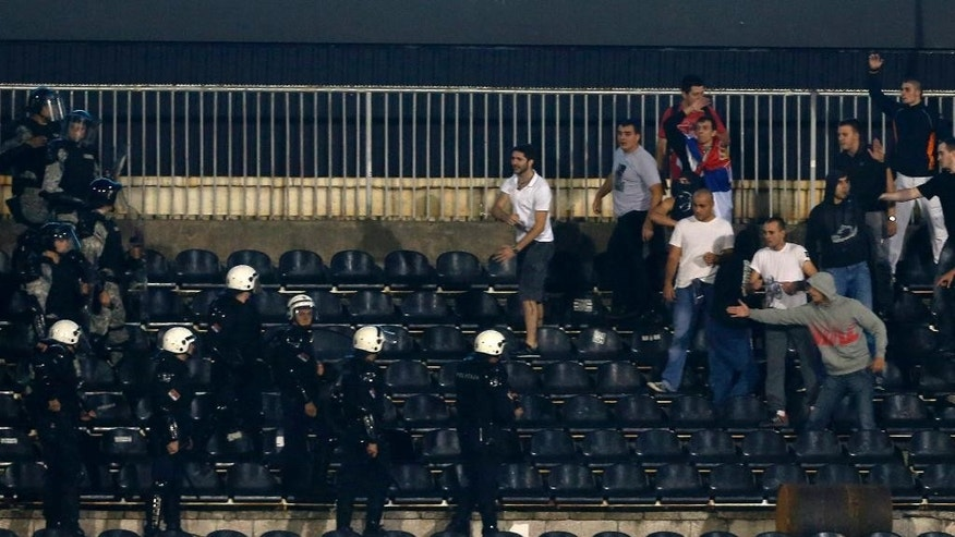Serbian riot police officers clash with soccer fans during the Euro 2016 Group I qualifying match between Serbia and Albania, at the Partizan stadium in Belgrade, Serbia, Tuesday, Oct. 14, 2014. The match was suspended. (AP Photo/Darko Vojinovic)