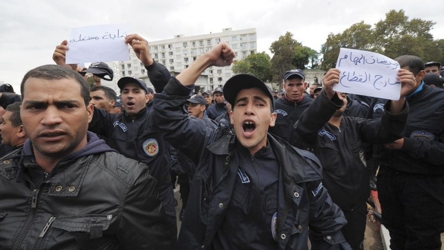 "Members of Algeria police force demonstrate outside the Algerian presidency, background at right, in Algiers, Wednesday, Oct. 15, 2014. Algerian police have marched to the president's headquarters in an unusual protest movement prompted by attacks on security forces. The attacks on police in southern Algeria and subsequent protests come amid concerns that President Abdelaziz Bouteflika is too ill to rule Africa's largest country. Poster at left reads: ""Independent Union"", and at right: ""We are on Strike"". (AP Photo/Sidali Djarboub)"