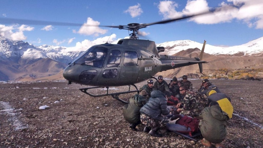 In this photo provided by the Nepalese army, soldiers prepare to airlift an avalanche victim in Thorong La pass area, Nepal, Wednesday, Oct. 15, 2014. An avalanche and blizzard in Nepal's mountainous north have killed at least 12 people, including eight foreign trekkers, officials said Wednesday. Five other climbers were hit by a separate avalanche on Mount Dhaulagiri and remain missing. (AP Photo/Nepalese Army)