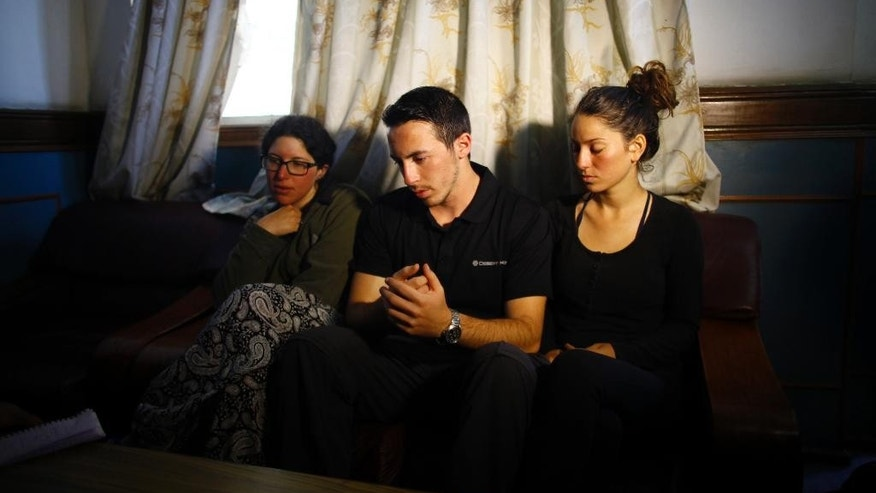 From left to right, Israeli trekkers Linor Kajan, Yakov Megreli and Maya Ora attend the media at the Army hospital in Katmandu, Nepal, Thursday, Oct. 16, 2014. Nepal army rescuers in helicopters spotted eight more bodies of trekkers along a mountain trail that was buried in avalanches and blizzards, raising the death toll to 20, while five more climbers were missing on another mountain, officials said Thursday. (AP Photo/Niranjan Shrestha)