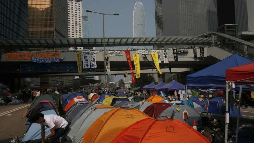 Pro-democracy protesters set up tents on a main road in an occupied area outside government headquarters in Hong Kong's Admiralty district Wednesday, Oct. 15, 2014. Hundreds of Hong Kong police officers drove protesters from a tunnel in the dead of night in the worst violence since the street demonstrations for greater democracy began more than two weeks ago. (AP Photo/Vincent Yu)