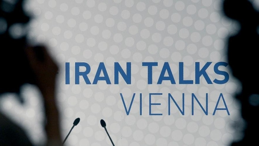 Video cameras stand in front of a poster of the Iran talks during closed-door nuclear talks at a hotel in Vienna, Austria, Tuesday, Oct. 14, 2014. With differences still unresolved and the deadline for a deal nearing, Iran and the U.S. have a choice to make: Extend nuclear talks for a second time or face the risk of renewed confrontation and armed conflict. U.S. Secretary of State John Kerry meets Wednesday in Vienna with Iranian Foreign Minister Mohammad Javad Zarif to try and advance the talks and meet the target date of Nov. 24. (AP Photo/Ronald Zak)