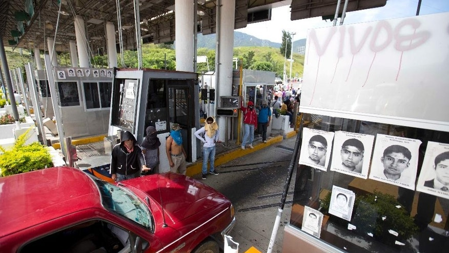 Masked student occupy a toll booth as students block a main highway to protest the disappearance of 43 missing college students in Chilpancingo, Mexico, Wednesday, Oct. 14, 2014. Mexican police expanded their search for the missing students Wednesday after investigators determined that 28 sets of human remains recovered from a mass grave were not those of any of the youths. (AP Photo/Eduardo Verdugo)