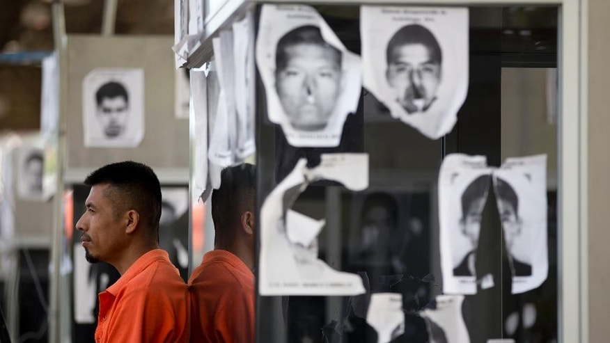 A man stands next to the pictures of missing students posted on a toll booth as students block a main highway to protest the disappearance of 43 missing college students in Chilpancingo, Mexico, Wednesday, Oct. 14, 2014. Mexican police expanded their search for the missing students Wednesday after investigators determined that 28 sets of human remains recovered from a mass grave were not those of any of the youths. (AP Photo/Eduardo Verdugo)