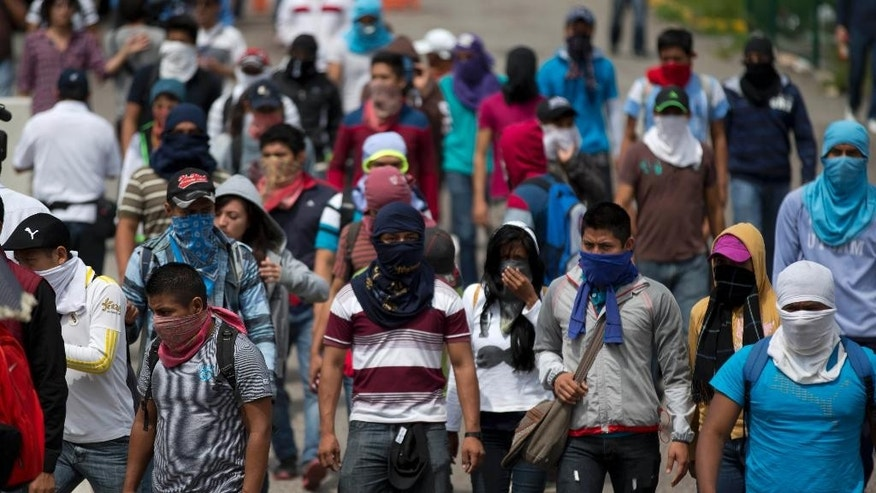 A masked students block a main highway to protest the disappearance of 43 missing college students, in Chilpancingo, Mexico, Wednesday, Oct. 14, 2014. Mexican police expanded their search for the missing students Wednesday after investigators determined that 28 sets of human remains recovered from a mass grave were not those of any of the youths. (AP Photo/Eduardo Verdugo)