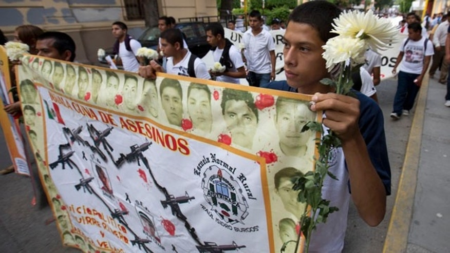 October 14, 2014: Students hold a banner with the faces of the missing that reads in Spanish 'cradle of murders'  during a march with flowers and candles to protest the disappearance of 43 students from the Isidro Burgos rural teachers college in Chilpancingo, Mexico. (AP Photo/Eduardo Verdugo)