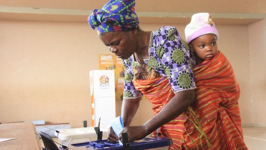 A woman with a child on her back casts her vote at a polling station as the country goes to the polls in Maputo, Mozambique, Wednesday, Oct. 15, 2014. The recent discovery of some of the world's largest gas and coal reserves in the southern African country has changed Mozambique's status from a war-torn country to one that is attracting international investment. The winner of this year's election will control natural resources worth billions of dollars. (AP Photo/Ferhat Momade)
